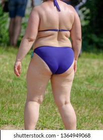 Fat woman in swimsuit on the beach.