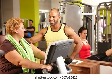 Fat woman training on exercise bike with personal trainer.