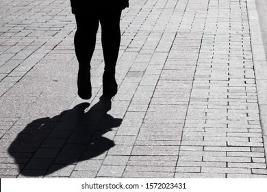 Fat woman walking down on a street, black silhouette and shadow on pavement. Concept of overweight, loneliness, parting, human life