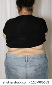 Fat woman weight 92 kg. Wear jeans standing behind.