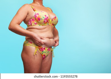 fat woman's body on blue background, healthy concept. folds in the abdomen. women's obesity and cellulite, overweight. model in a swimsuit. women's waist. space. - Image
