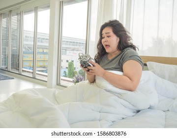 Fat women are panicked after watching the alarm clock. Because it's late for her work, causing her to go late today.