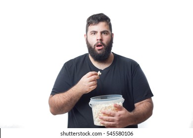 Fat young man with black t-shirt and bowl of popcorn and surprised face isolated on white background