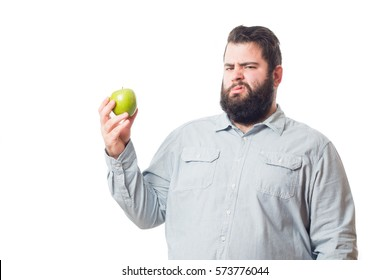 Fat young man holding an apple isolated on white background
