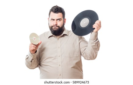 Fat young man holding a vinyl in one hand and in the other holds a cd isolated on white