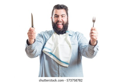 Fat young man with a napkin in the neck of his shirt holding a knife and a fork isolated on white background