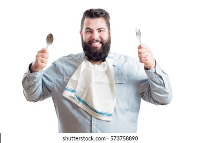 Fat young man with a napkin in the neck of his shirt holding a spoon and a fork isolated on white background