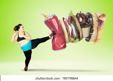 Fat young woman kicking fast foods and a can of soft drink while wearing sportswear. Shot with green screen background