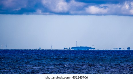 Fata Morgana (mirage) of coastline with wind turbines on it