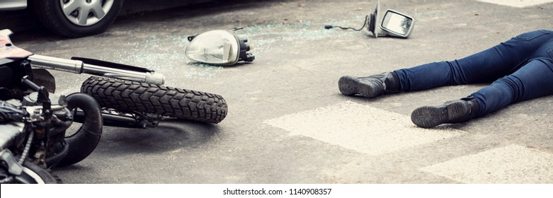 Fatal aftermath of a car accident concept - dead body and crashed motorcycle parts lying on the road