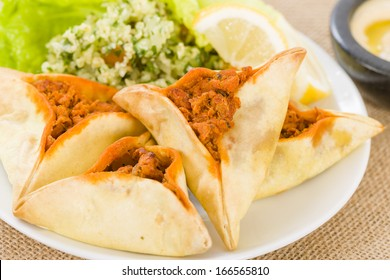 Fatayer - Arab pastry filled with spicy meat. Served with tabbouleh and lemon wedges.