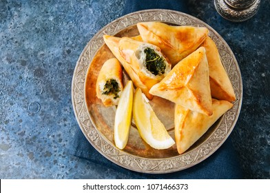 Fatayer sabanekh - traditional arabic spinach triangle hand pies in a vintage plate on a blue stone background. Top view.