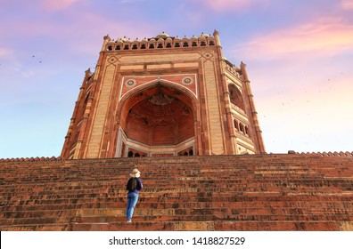 "Fatehpur Sikri - Female tourist looks up at the giant Mughal architecture gateway known as the ""Buland Darwaza"" at Fatehpur Sikri at sunset"