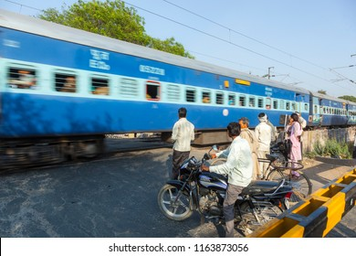 FATEHPUR SIKRI, INDIA - NOV 16, 2011: people wait at the railway crossing near Fatehpur Sikri, India to cross the street.