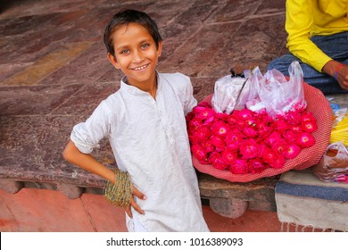 FATEHPUR SIKRI, INDIA-NOVEMBER 9: Unidentified boy sells flowers in the courtyard of Jama Masjid on November 9, 2014 in Fatehpur Sikri, India. The mosque was built in 1648 by Emperor Shah Jahan