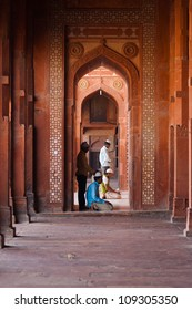 Fatephur Sikri, India - November 18, 2009: Muslims praying, kneeling inside the red sandstone doorway and hall of the fort mosque for afternoon prayers