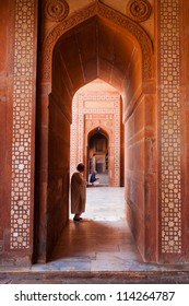 Fatephur Sikri, India - November 18, 2009: Muslim man standing, praying inside a red sandstone hall doorway at the fort mosque for afternoon prayers