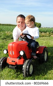 Father and 2 years young son playing with tractor