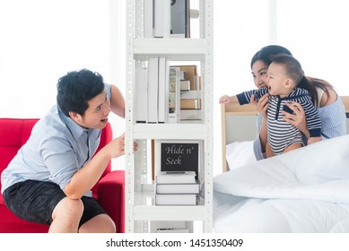 Father and 8 months old baby play hide and seek through book shelf, black book cover edited for hide and seek concept