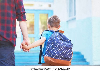 father accompanies the child to school. a man with a child removed from the back. doting dad holding the hand of her son going to school. the boy is going to primary school with pleasure