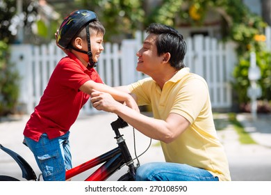 Father adjusting helmet of his son before biking