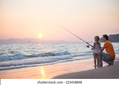 Father with adorable daughter fishing with rod on ocean beach on sunset