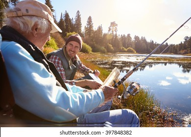 Father and adult son fishing lakeside, close-up