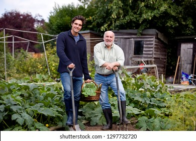 Father with adult son working on allotment together smiling at camera