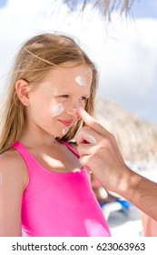 Father applying sun cream to daughter nose. Portrait of cute girl in suncream