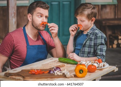 Father in apron and cute little son having fun with pepper moustaches, dad and son cooking concept
