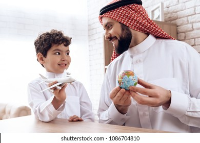 Father Arab tells son about flight of aircraft. Boy is played by model aircraft. Study of geography.
