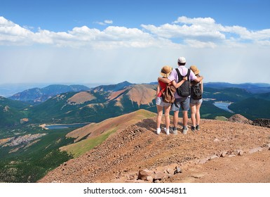 Father with arms around his family looking at beautiful  mountains landscape, on hiking trip, on  top of  mountain rock. View from the top of Pikes Peak.  Pike National Forest, Cascade, Colorado, USA