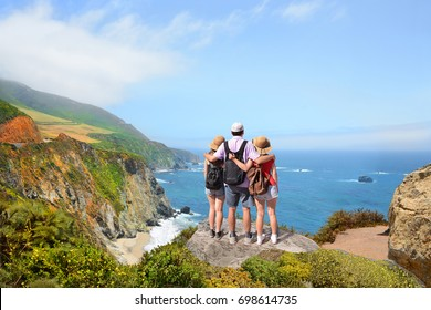 Father with arms around his family  looking at beautiful  ocean view,people on hiking trip in the mountains. View from   highway 1 in California over Pacific Ocean. Big Sur, California, USA