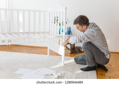 Father assembly crib for the newborn child, his cat is curious and looking whats going on