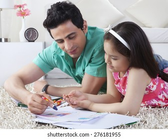 Father assisting girl in drawing while lying on rug at home