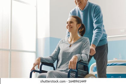 Father assisting her daughter in wheelchair at the hospital, family and healthcare concept