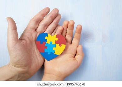 Father and autistic son hands holding jigsaw puzzle heart shape. Autism spectrum disorder family support concept. World Autism Awareness Day