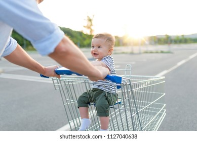 Father with baby boy in the car park, going shopping. Beautiful and adorable baby in shopping cart.  Middle age father with his little son.  Baby sit in supermarket cart