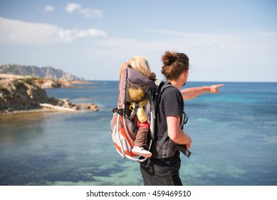 Father and baby daughter in backpack carrier looking at scenic view. Family travel