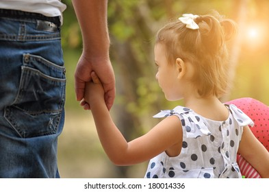 Father and baby girl holding hand in hand