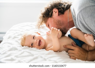 Father and baby girl on a bed