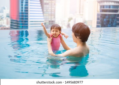 Father and baby girl swimming in a pool. infants swimming. Asian Baby swimming concept.