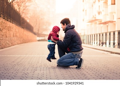 Father and baby have quality time together. Dad holding toddler outdoors, sunset spring portrait. Tender, parenthood, father-child bond