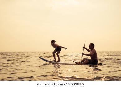 Father and baby son playing on the beach at the day time. People having fun outdoors. Concept of summer vacation and friendly family.