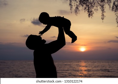 Father and baby son  playing on the beach at the sunset time. People having fun outdoors. Concept of summer vacation and friendly family.