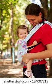 Father and baby walking outdoors in an urban neighborhood. Happy baby sitting in a carrying sling. Father nursing baby. Happy family.