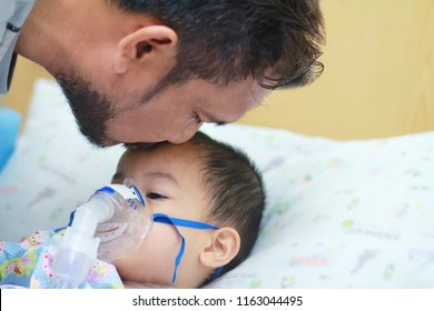 Father with beard and mustache kiss his little son while he had  nebulizations,Sick boy rest on patien bed and has inhalation therapy by the mask of inhaler.Sick or cancer child awareness.