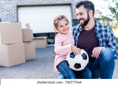 father and beautiful daughter with soccer ball sitting in front of new house