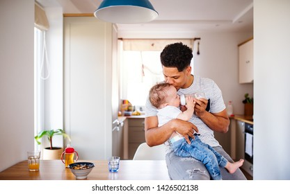 A father bottle feeding a small toddler son indoors at home.