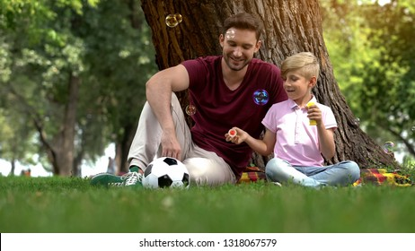 Father and boy enjoying making bubbles in park, family entertainment in weekend